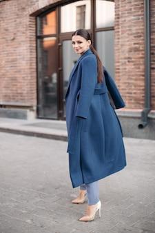 Vista laterale per tutta la lunghezza dell'attraente signora bruna con la coda che indossa cappotto blu, pantaloni azzurri e tacchi bianchi. si sta muovendo e sorride alla telecamera in una strada urbana.