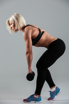 Side view full length portrait of a muscular adult sportswoman