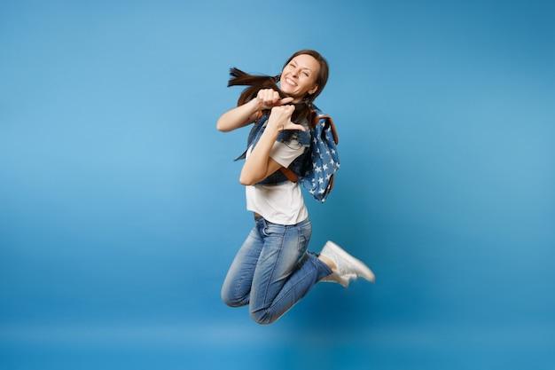 Вид сбоку полнометражный портрет молодого смеющегося студента женщины в джинсовой одежде при прыжки рюкзака показывая большие пальцы руки вверх изолированный на голубой предпосылке. обучение в колледже. скопируйте место для рекламы.