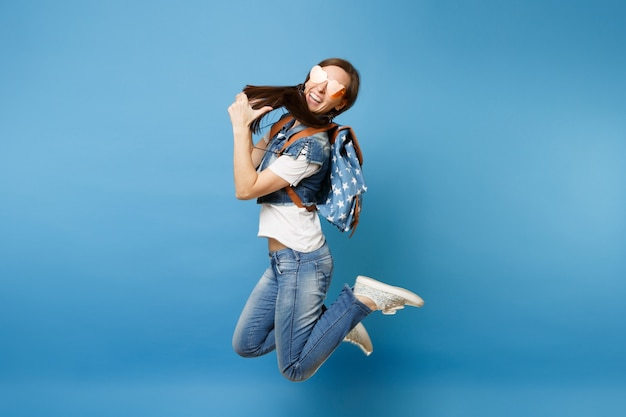 Вид сбоку полнометражный портрет молодого смеющегося студента женщины в оранжевых очках сердца, прыгающих, показывая большой палец вверх изолированный на синем фоне. обучение в университете. скопируйте место для рекламы.