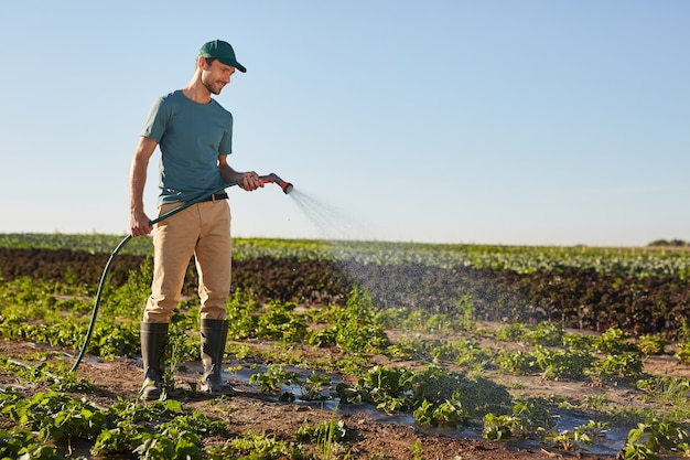 Side view full length portrait of young male worker watering crops at vegetable plantation and smiling while standing outdoors against blue sky, copy space