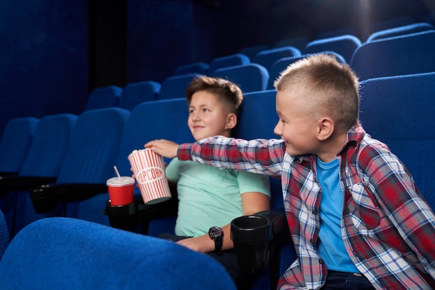 Side view of funny boys watching comical movie together in cinema