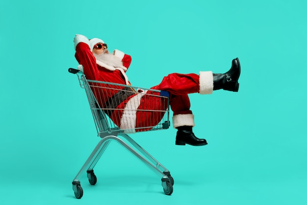 Side view of funny santa claus in black sunglasses and costume making faces. old man having fun, sitting and relaxing in shopping cart