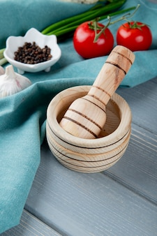 Side view of garlic crusher with vegetables and black pepper on blue cloth surface and wooden background