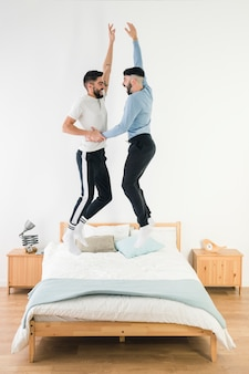 Side view of gay couple enjoying jumping on bed in the bedroom