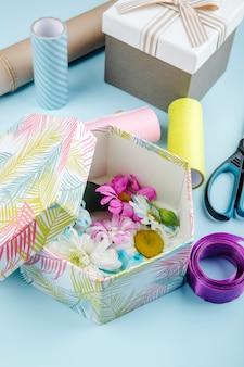 Vista laterale di una confezione regalo piena di fiori colorati di crisantemo con rotoli di margherita e forbici di carta e nastro viola su sfondo blu