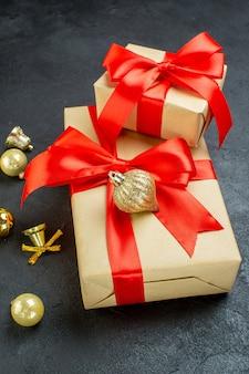 Vista laterale della confezione regalo con nastro rosso e accessori di decorazione su sfondo scuro