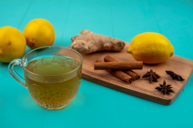 Side view of ginger juice in glass and spices as ginger and cinnamon with lemon on cutting board on blue background