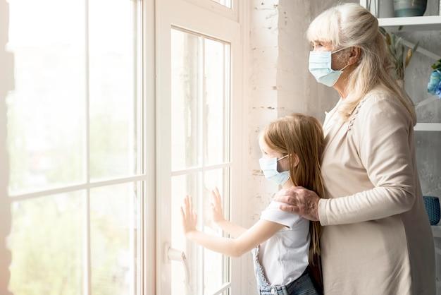 Вид сбоку девушка и бабушка с маской