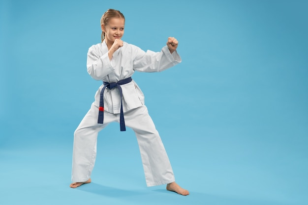 Side view of girl doing martial arts on isolated background