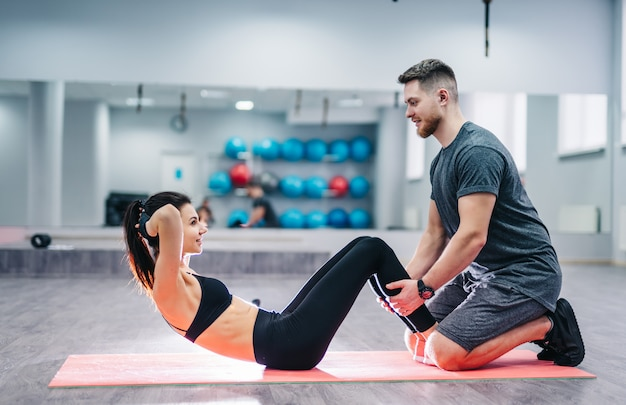 Side view of a girl doing press exercises on the mat with the help of a smiling male.