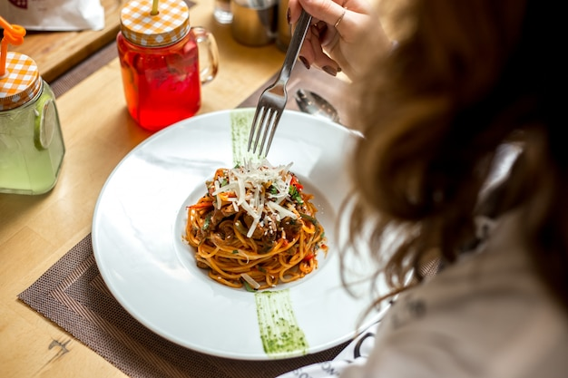 Side view a girl eats spaghetti with meat and grated cheese
