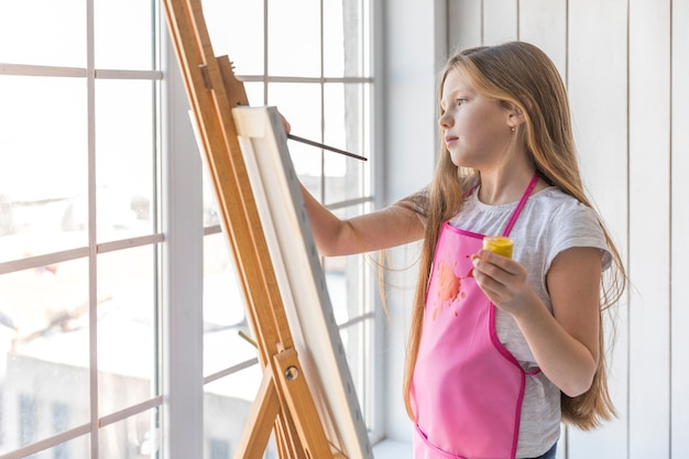 Side view of a girl holding yellow paint bottle in hand painting on the easel with paintbrush