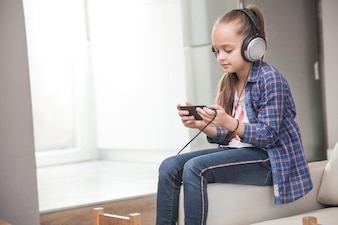 Side view girl in headphones using smartphone