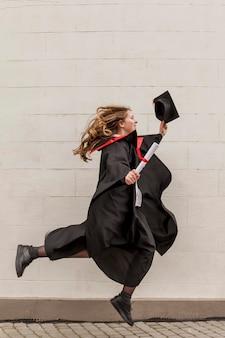 Вид сбоку девушка прыгает на выпускной