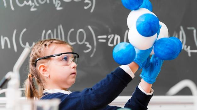 Ragazza di vista laterale che impara chimica