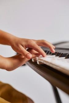Vista laterale della ragazza che impara a suonare la tastiera elettronica
