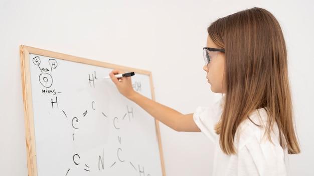 Vista laterale della ragazza che impara la scienza con la lavagna