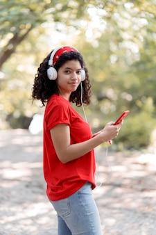 Вид сбоку девушка слушает музыку