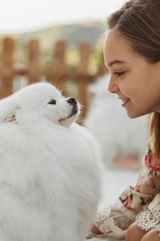 Вид сбоку девушка смотрит на свою собаку