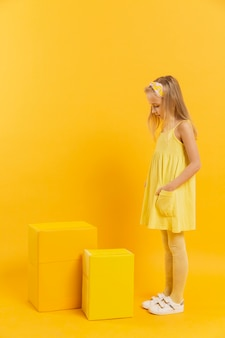 Side view of girl looking at yellow stools with copy space