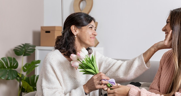 Вид сбоку девушка предлагает цветы маме