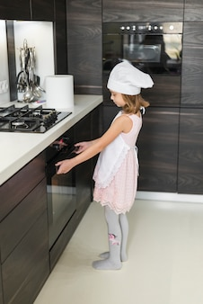 Side view of girl opening oven while baking in kitchen