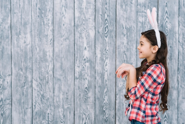 Side view of a girl posing like rabbit in front of gray wooden backdrop
