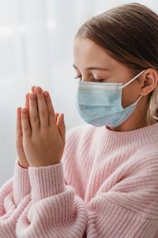Vista laterale della ragazza che prega con mascherina medica