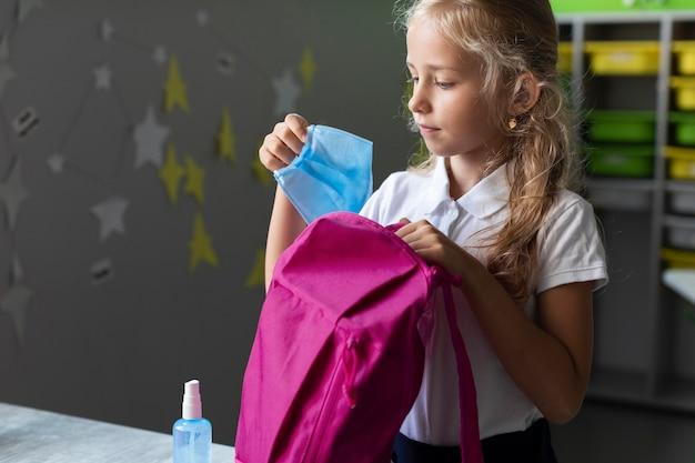 Вид сбоку девушка кладет медицинскую маску в рюкзак