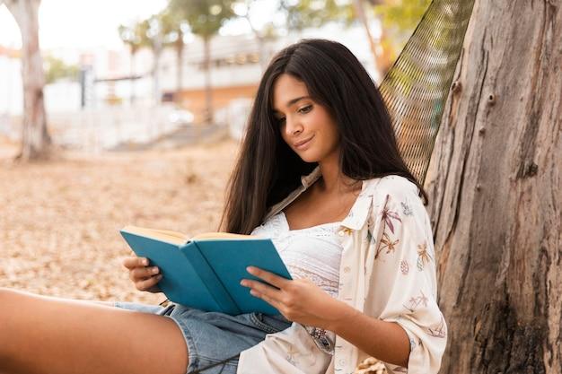 Вид сбоку девушка читает в гамаке