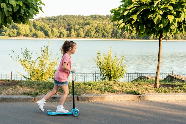 Side view of girl riding blue scooter