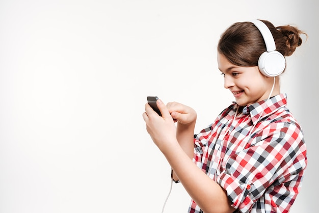 Side view of girl in shirt listening music