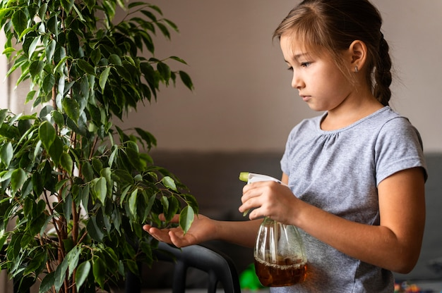 Side view of girl spraying plant with water