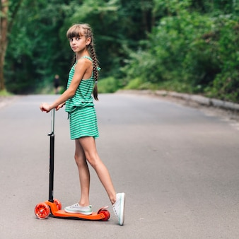 Side view of a girl standing over the scooter on road