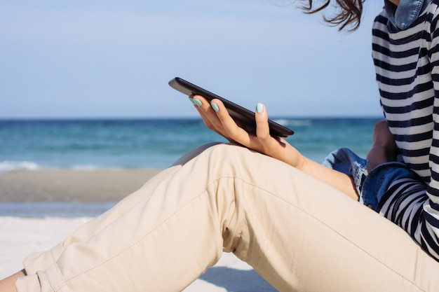 Side view of a girl in a striped t-shirt and beige pants on the beach which is reading a book