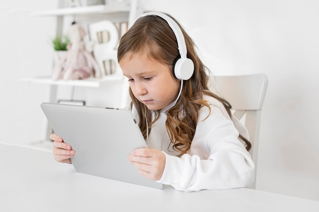 Side view of girl using tablet with headphones