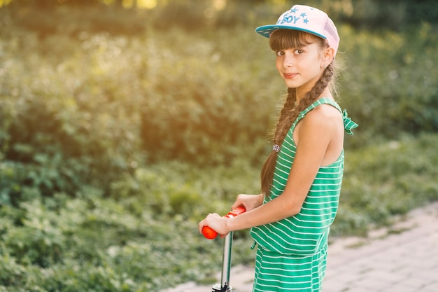 Side view of a girl wearing cap standing on kick scooter