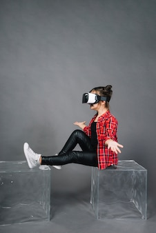 Side view of a girl wearing virtual reality goggles shrugging