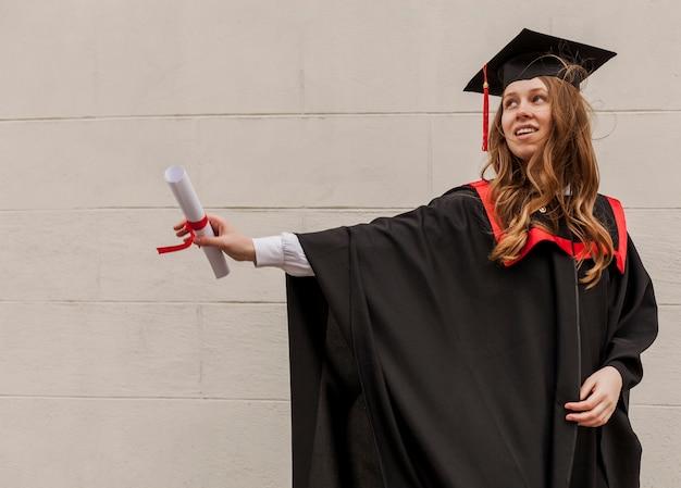 Боковой вид девушка с дипломом