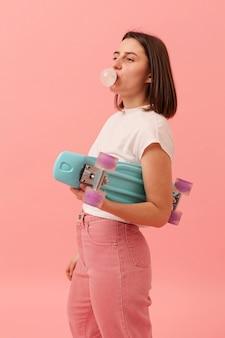 Вид сбоку девушка со скейтбордом