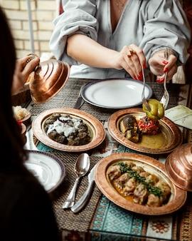 Вид сбоку девушки едят долма и голубцы с йогуртом