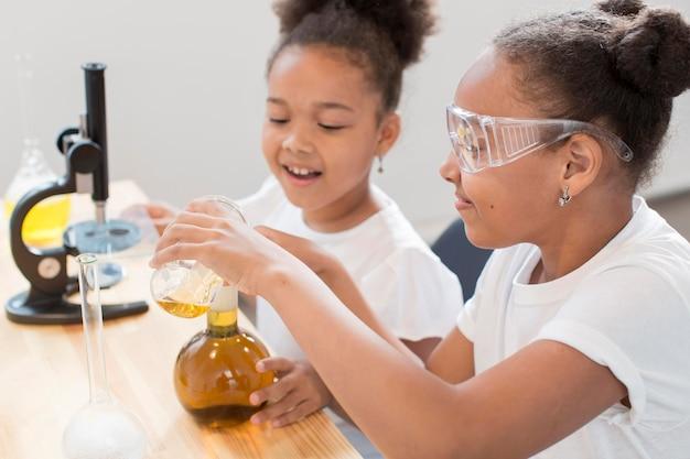 La vista laterale delle ragazze sperimenta la chimica a casa