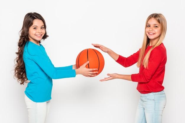 Вид сбоку девушки играют с баскетбольным мячом