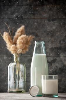 Vista laterale della bottiglia di vetro e della tazza riempita con tappo per il latte su sfondo scuro