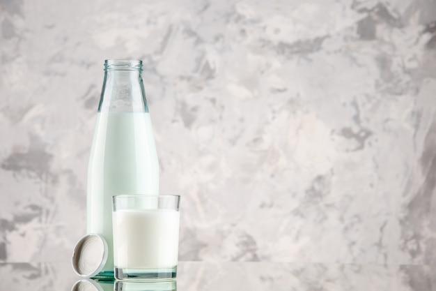 Vista laterale della bottiglia di vetro e della tazza riempita con tappo per il latte sul lato destro su sfondo di colori pastello con spazio libero