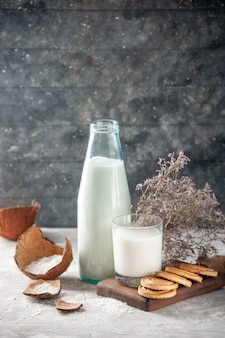 Vista laterale della bottiglia di vetro e della tazza riempita di latte sul fiore del vassoio di legno sulla parete scura