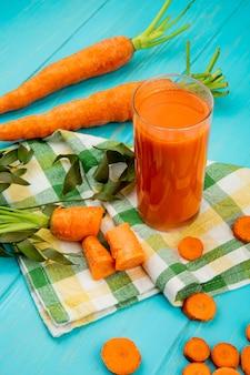 Vista laterale del bicchiere di succo di carota con carote tagliate e affettate sul panno decorato con foglie sul tavolo blu