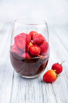 Side view of a glass of chocolate milkshake with strawberries on a grey wooden surface