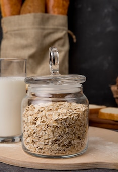Side view of glass jar with oat-flakes and milk on wooden surface and black background with copy space